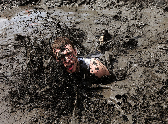 Man falling in the mud with a funny look on his face